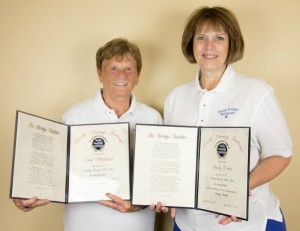 Enid Whittaker (left) and Sandy Dirks (right) hold their certificates as inductees into the Massage Hall of Fame (2015)